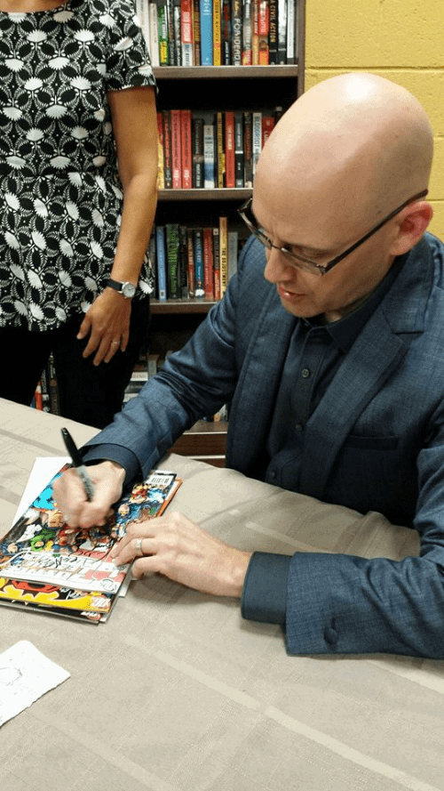 Brad Meltzer, author of Justice League comics and graphic novels, the Ordinary Heroes children's book series and political thrillers, signs our books at an author event at Flyleaf Books.