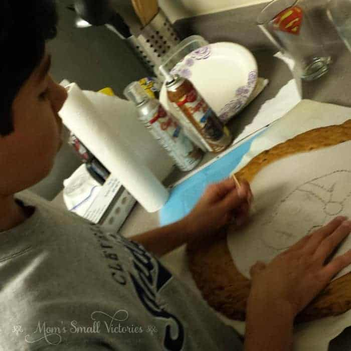 You can draw a design on a piece of wax or parchment paper and then poke a toothpick along the lines of the design through the paper and cake. Remove the paper and fill in the sections with icing for a more complicated cookie cake design.