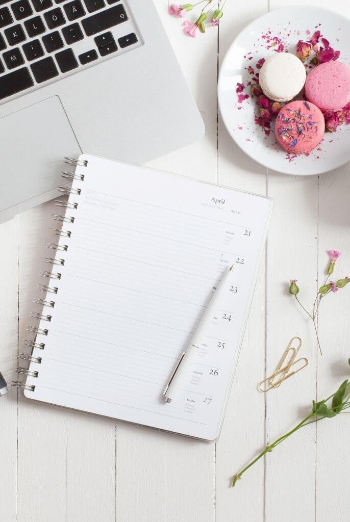 open weekly planner on top of a white desk with laptop, a plate of pink and white macarons and some flower branches